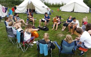Schülergruppe sitzt im Kreis zwischen Zelten, zwei Schüler haben Gitarren in der Hand.