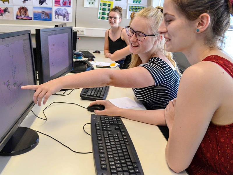 Schülerinnen am Rechner bei Projektarbeit Corporate Design am Technischen Gymnasium