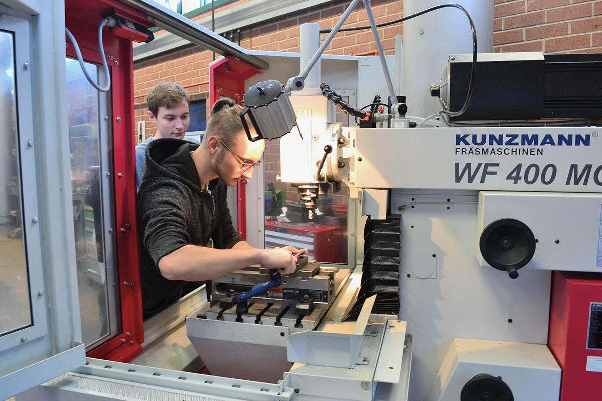 Zwei Berufsschüler arbeiten an Fräsmaschine