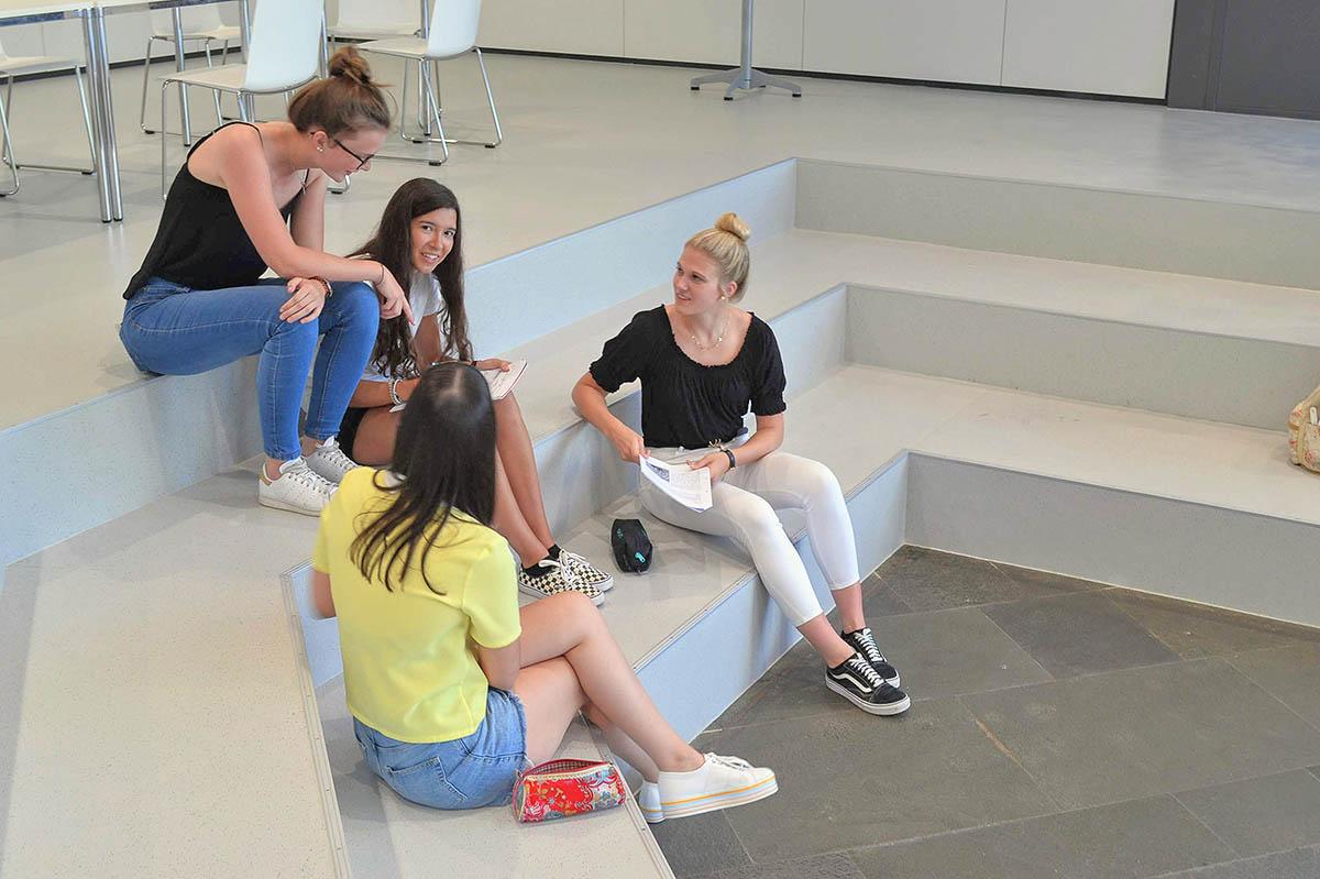 Schülerinnen unterhalten sich, sitzen im Schulcampus auf Treppe