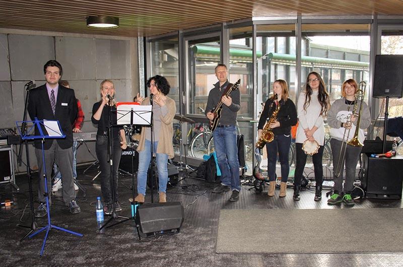 Gruppenbild der Schulband, 8 Personen mit Instrumenten oder Mikrophonen